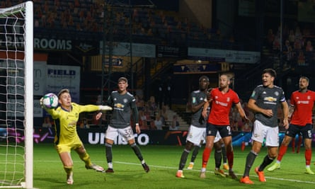 Manchester United goalkeeper Dean Henderson claws the ball away after a header by Tom Lockyer of Luton Town.