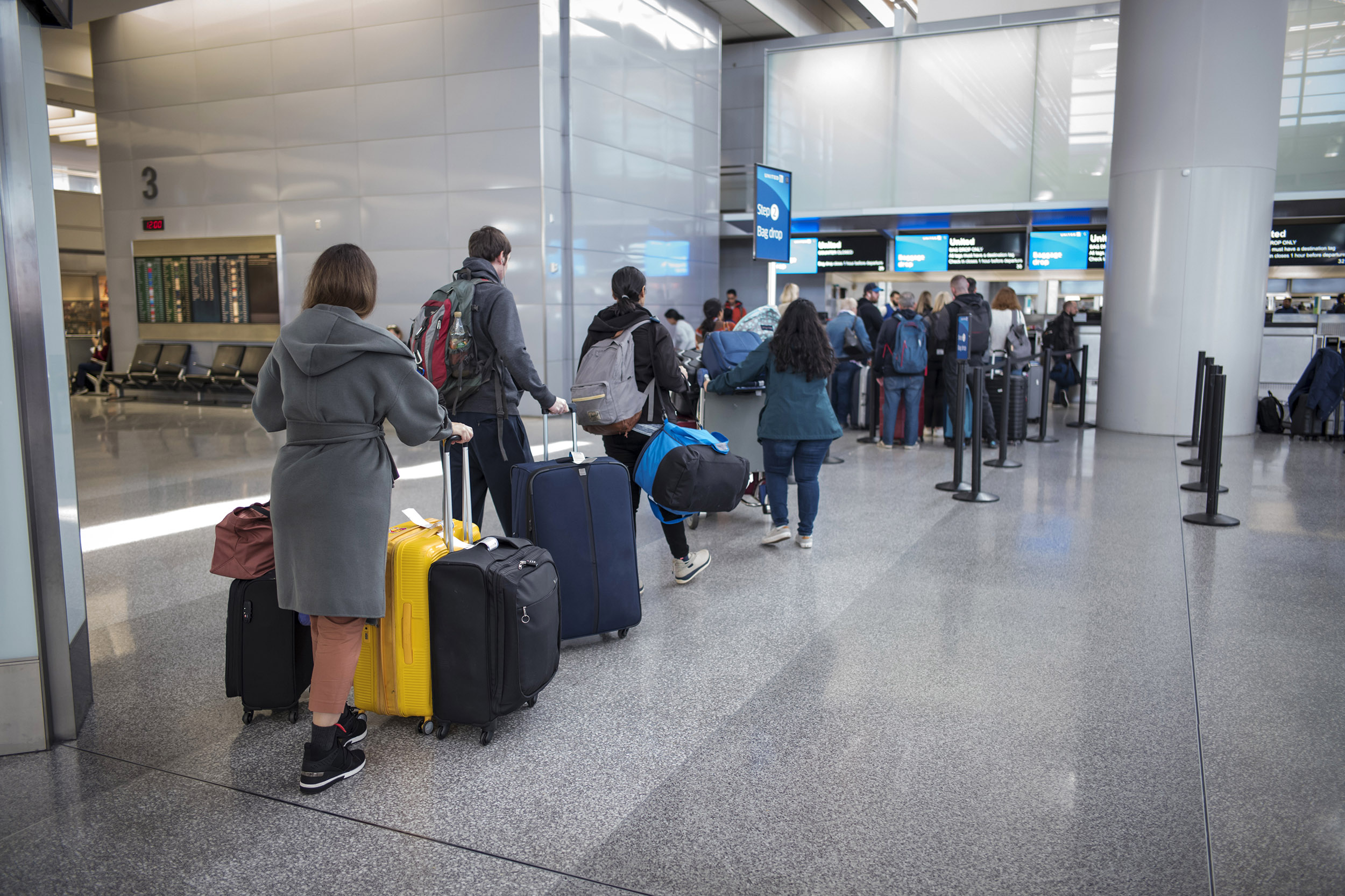 Travelers wait to check their bags at San Francisco International Airport in San Francisco, California, on Friday, January 31, 2020.
