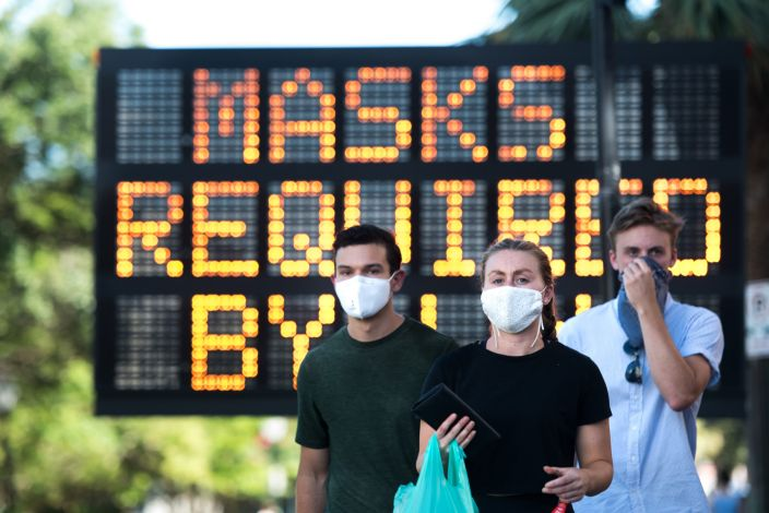 People wearing protective face masks walk along King St. in Charleston, S.C.
