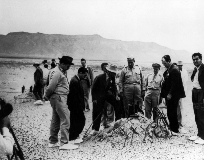 """Manhattan Project officials, including Robert Oppenheimer (white hat), inspect the remains of the Trinity atomic test in 1945. <p class=""""copyright"""">Los Alamos National Laboratory/The LIFE Picture Collection/Getty Images</p>"""