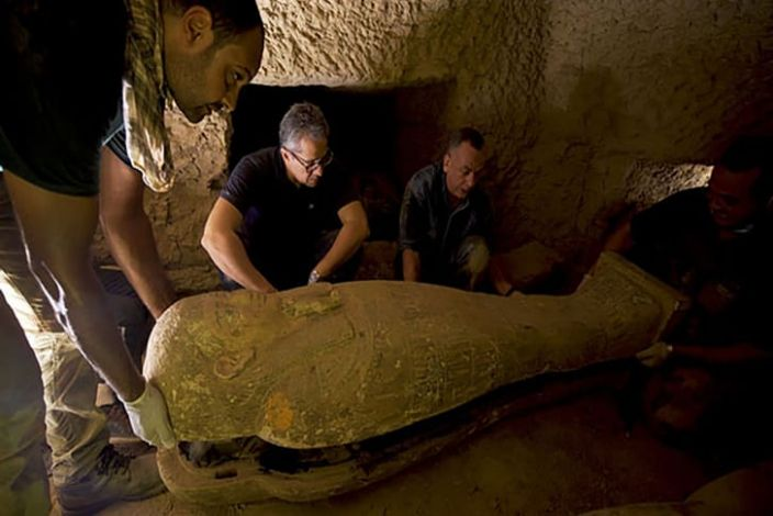 """Khaled El-Enany, Egypt's minister of tourism and antiquities, and Mostafa Waziri, the secretary-general of the Supreme Council of Antiquities, peer at a sarcophagi in Saqqara. <p class=""""copyright"""">Ministry of Tourism and Antiquities Egypt</p>"""