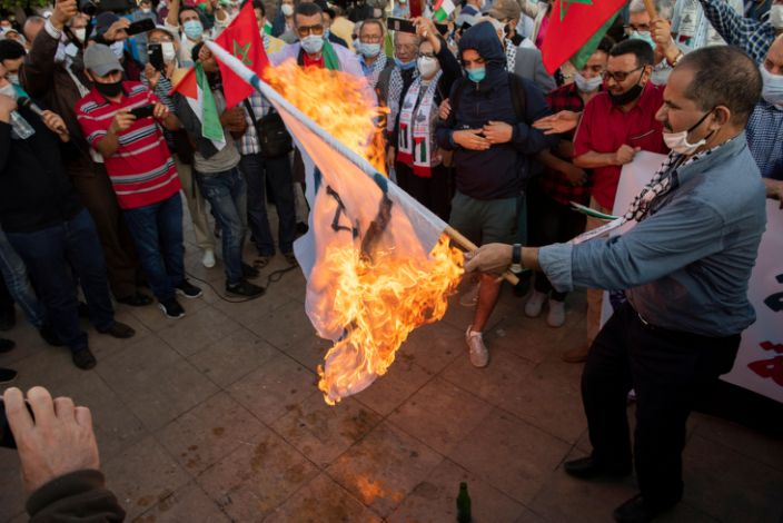 On Friday, people in the Moroccan capital, Rabat, burn an Israeli flag during a protest against the prospect of normalising relations with the country.