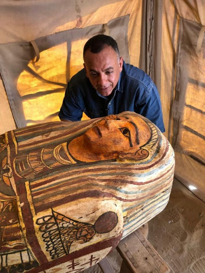 """Mostafa Waziri, secretary-general of Egypt's Supreme Council of Antiquities, looks at a 2,500-year-old coffin discovered in a burial shaft near Saqqara necropolis. The image was released September 19, 2020. <p class=""""copyright"""">The Egyptian Ministry of Antiquities/Handout via Reuters</p>"""