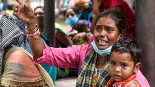 A woman holding a child reacts as she sits with migrant labourers during a protest held against the government's coronavirus measures