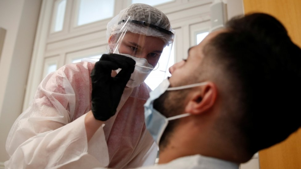 Health worker tests someone for coronavirus in Paris