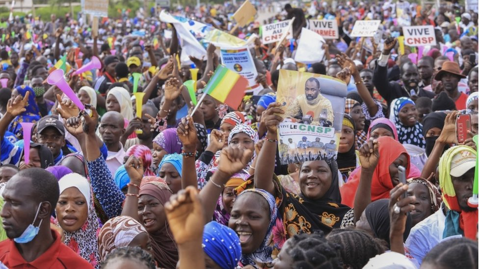 A Malian woman holds a poster with the image of Colonel Assimi Goita, the president of the National Committee for the Salvation of the People (CNSP), as she attends a mass gathering of supporters at Independence Square in Bamako on 8 September 2020.