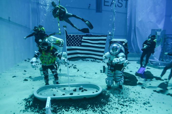 """Astronauts examine a flag placed in sand, one of a series of exercises being prepared for the Artemis Mission at NASA's Neutral Buoyancy Lab in Houston, Texas. <p class=""""copyright"""">NASA</p>"""