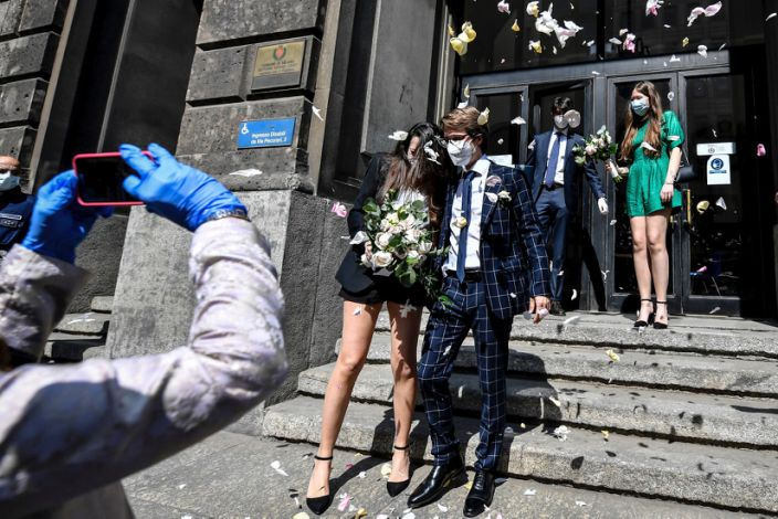 """A just married couple leaving the registry offices after their civil ceremony in Milan, Italy, Friday, May 8, 2020. Milan restarted civil marriages Thursday, as the city is slowly returning to life. Access to the ceremony is only allowed for best men. <p class=""""copyright"""">Claudio Furlan/LaPresse via AP</p>"""