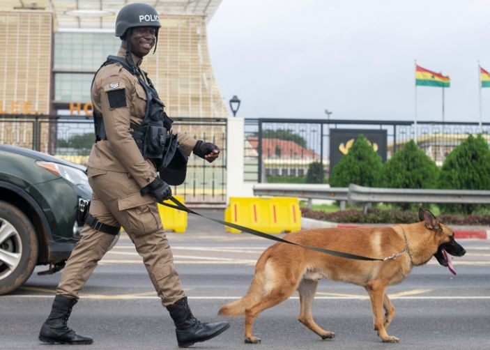 On the previous day, a dog walks with his handler as Ghana police officers take a confidence-building march through the streets of the capital, Accra, ahead of the general elections in December.