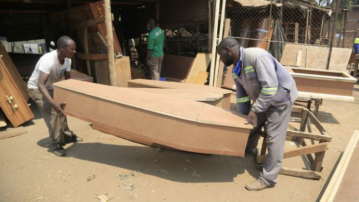 On Friday, coffin makers in Harare, Zimbabwe, prepare to put the finishing touches to their work.