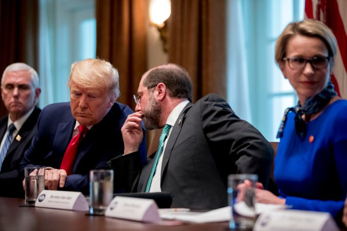 Health and Human Services Secretary Alex Azar, center, accompanied by Vice President Mike Pence, left, whispers with President Donald Trump, during a meeting with pharmaceutical executives on the coronavirus.