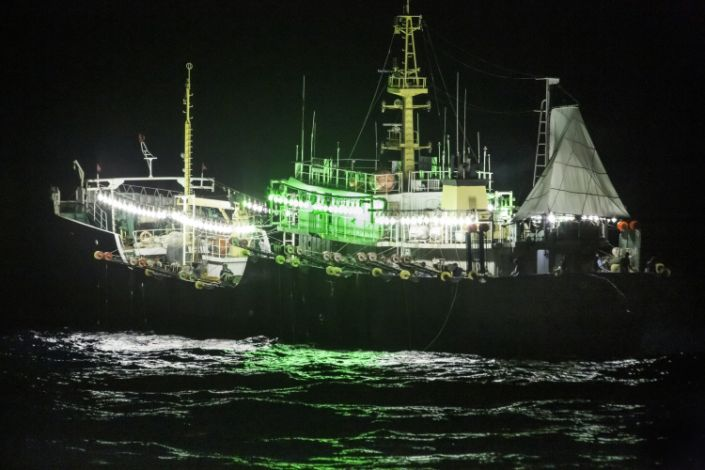 A ship with bright lights strung around its perimeter in the middle of the night