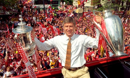 Wenger poses with the FA and League Cups in 1998, the first year that Arsenal did the double under Wenger.