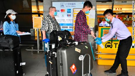 A worker sprays sprays hand sanitiser onto passengers as they arrive at Taoyuan Airport in Taiwan.