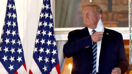 US President Donald Trump removes his mask on his return to the White House from Walter Reed National Military Medical Center, where he was treated for coronavirus.