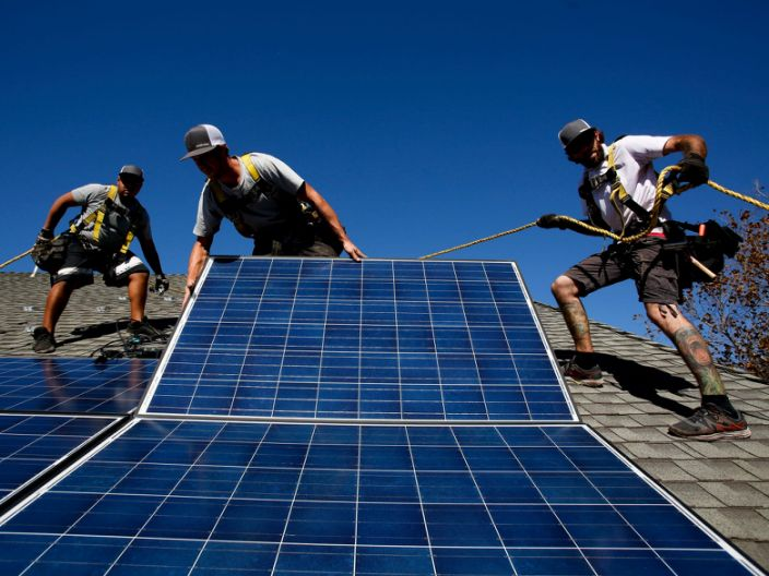 """Vivint Solar workers install rooftop solar panels <span class=""""copyright"""">Anne Cusack/Los Angeles Times via Getty Images</span>"""