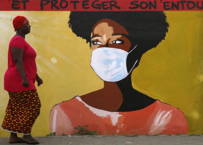 People pass a mural painted on a wall meant to sensitize the locals on how to prevent themselves from contracting and spreading the COVID-19 coronavirus, in Abidjan, Ivory Coast, 22 October 2020.