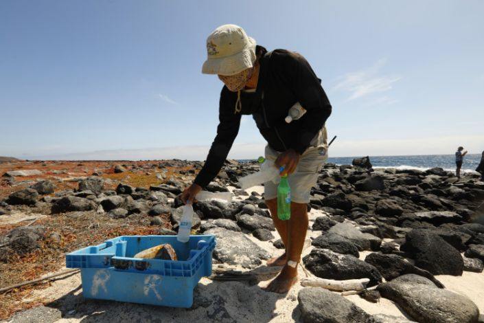 A man picks up plastic bottles and puts them in a blue bin on a rocky island beach