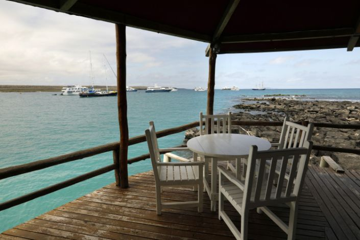 Empty tables on a wooden deck overlooking blue water in the Galapagos Islands