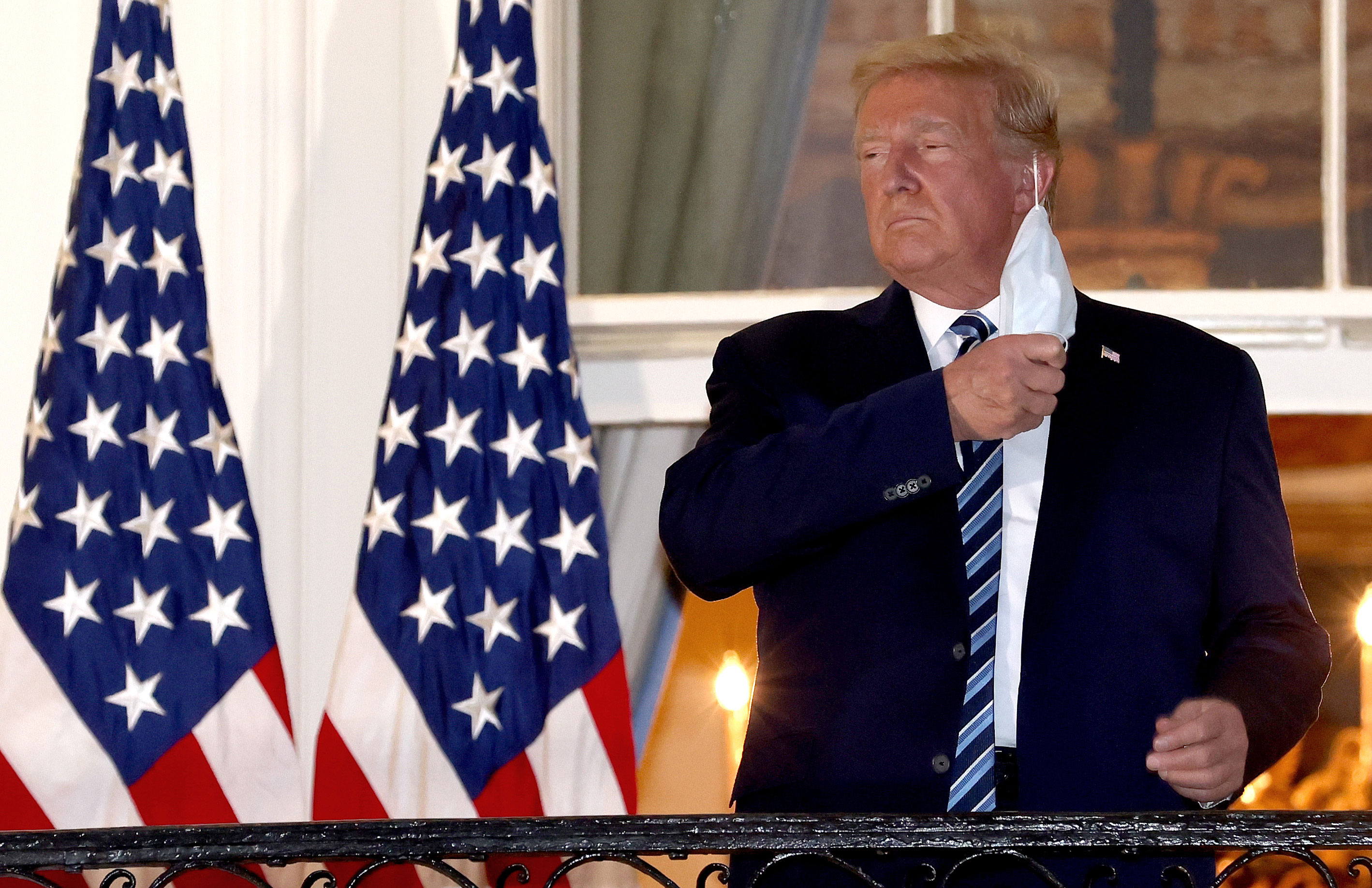 President Donald Trump removes his mask upon returning to the White House from Walter Reed National Military Medical Center on October 5.