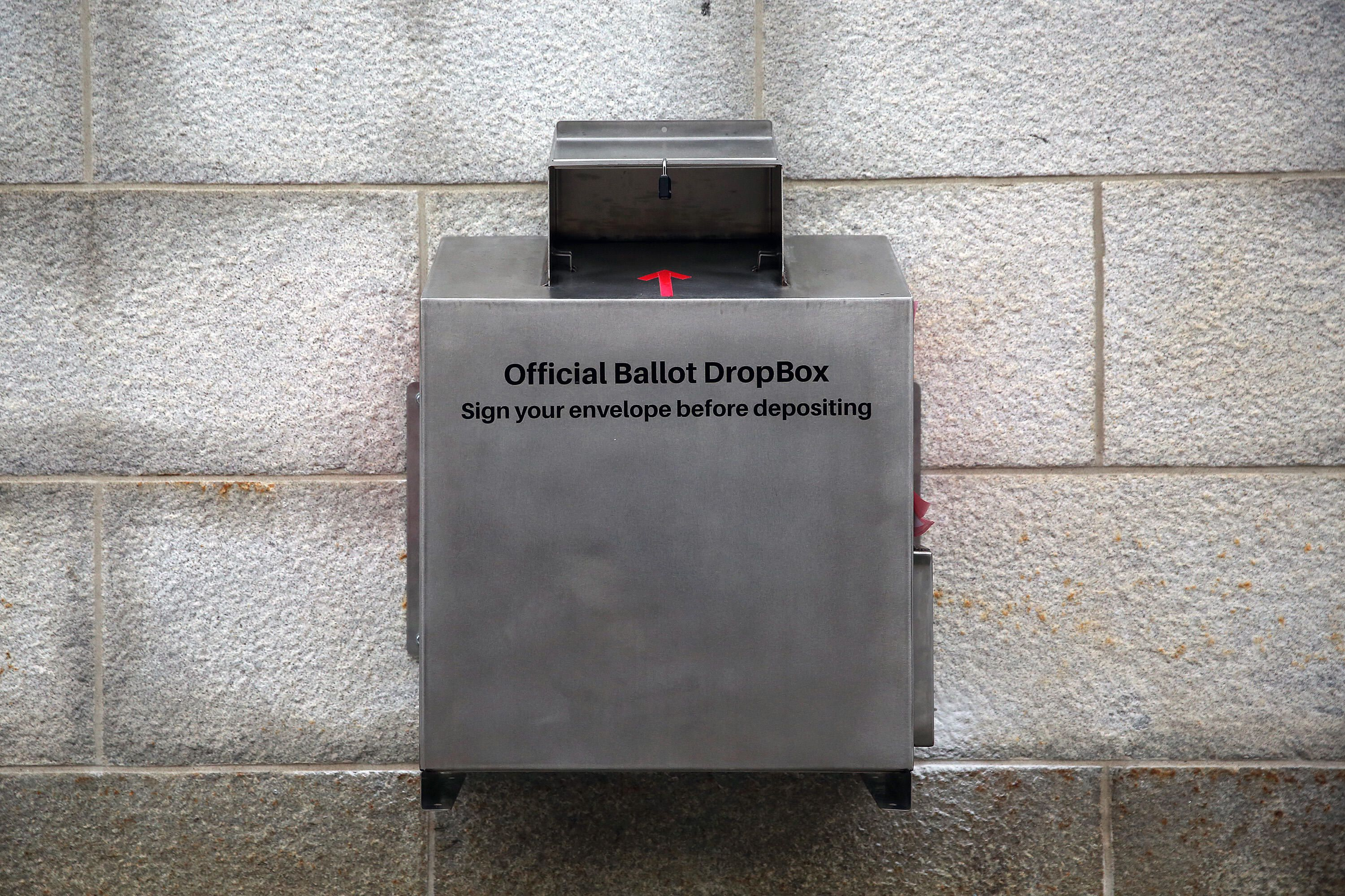 A ballot drop box with a sign that says