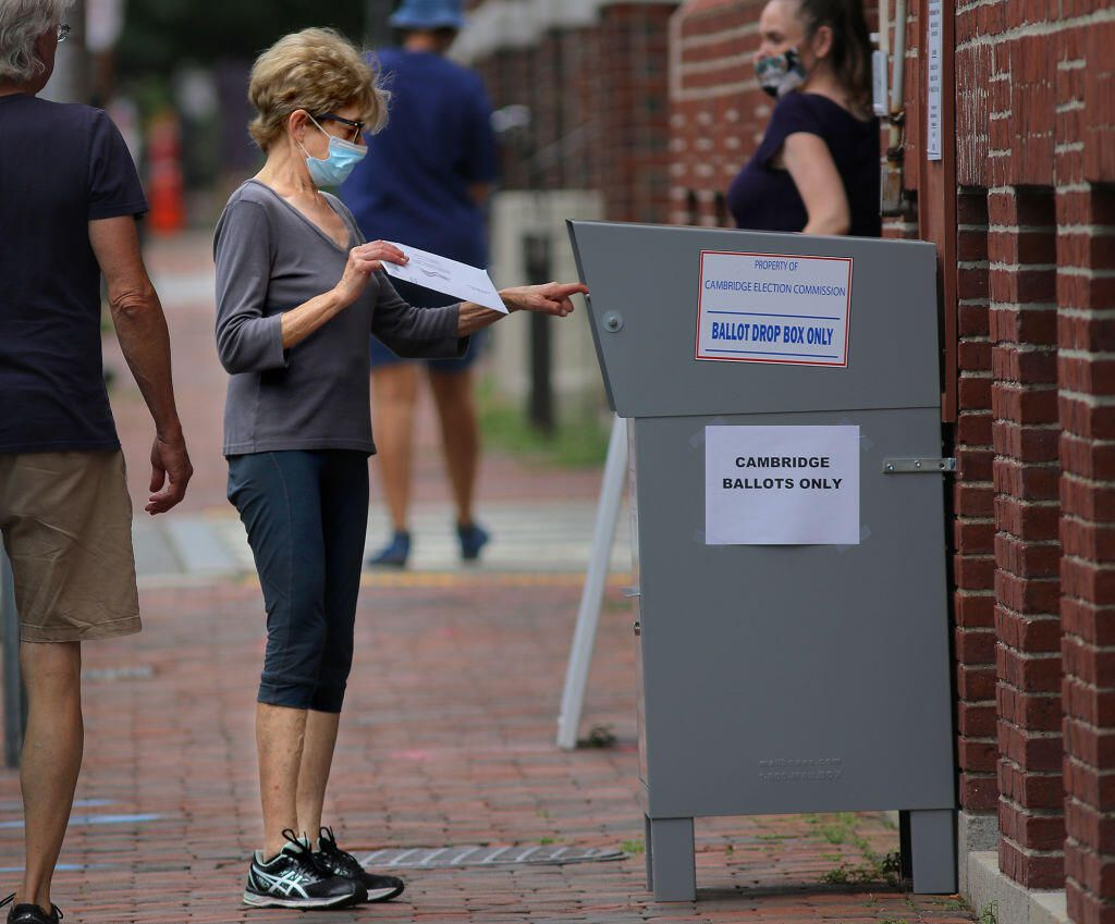 A voter drops a vote-by-mail ballot into a collection box in Massachusetts.