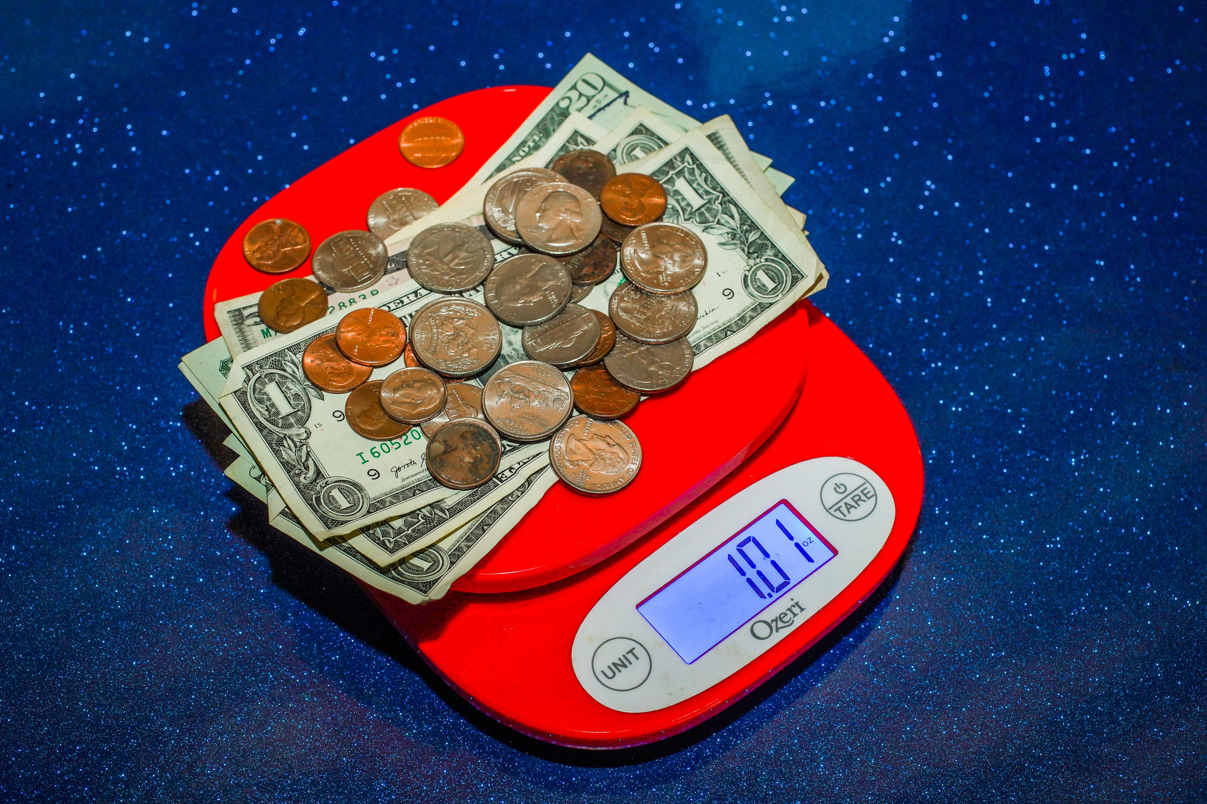011-stimulus-piggy-bank-tear-falling-money-clip-weighing-cash-scale